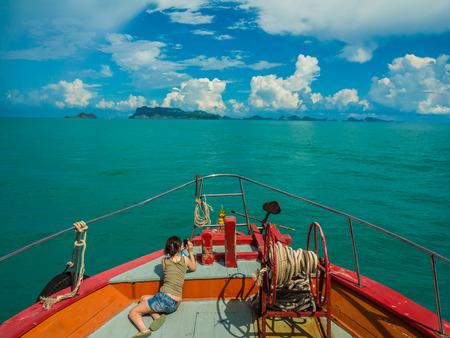 Tourist taking photo on bow of ferry boat heading to Samui Island photo