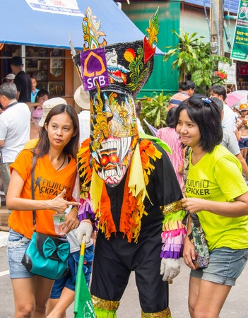 folkways: Tourist taking photo with colorful mask performer in Phi Ta Khon Festival, Loei, Thailand