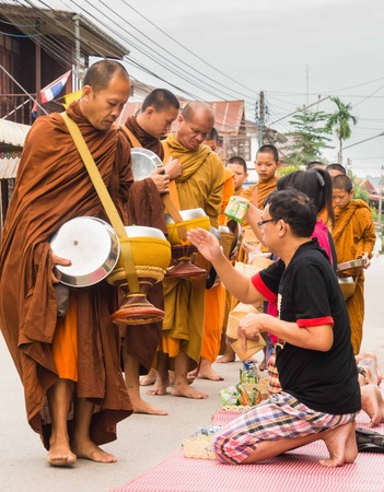 khan: Unidentified tourists offering sticky rice to Buddhist monk in  Chiang Khan Editorial