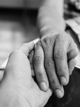 gerontology: Hands of mother and son holding together