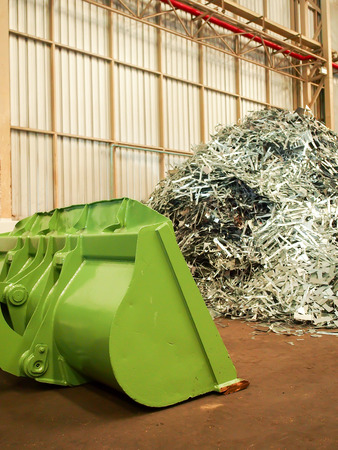 discarded metal: Metal scrap pile and big dozer in recycle factory Stock Photo