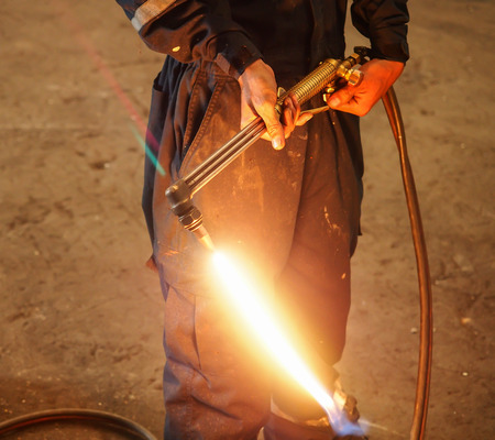 acetylene: Worker with Oxygen Acetylene metal cutting torch in recycle factory Stock Photo