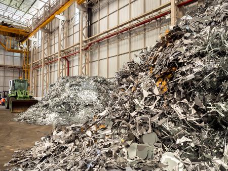 金属スクラップの山とリサイクル工場でブルドーザー