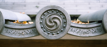 Mitsudomoe symbol on Shinto Buddhist shrine roof tile in Japan
