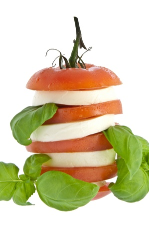 Stacked tomato with mozzarella and fresh basil isolated on white  photo