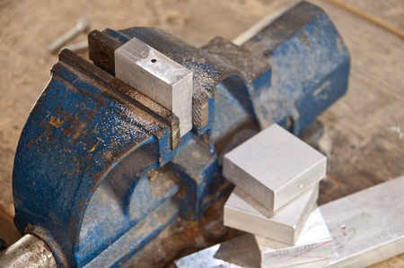 Vice with a block of metal on a wooden workbench Stock Photo - 12603470