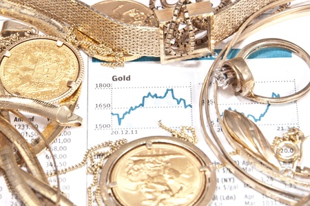 Old jewelry and gold coins with printed gold chart in background photo