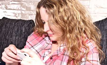 Young attractive woman is lying on the couch, using a mobile phone and listening to music photo