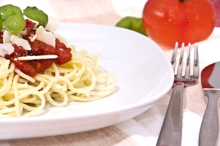 Fresh homemade spaghetti with parmesan cheese and basil on a plate with fork and knife photo