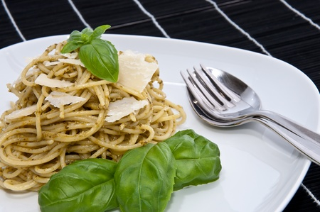 Heap of spaghetti on a plate with fresh homemade pesto, basil, Parmesan and cutlery on a black tablecloth photo