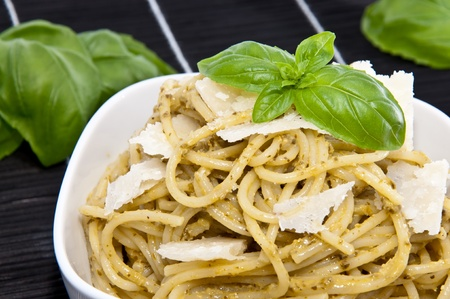 Spaghettis in a bowl with fresh pesto sauce, basil and Parmesan on a black tablecloth photo