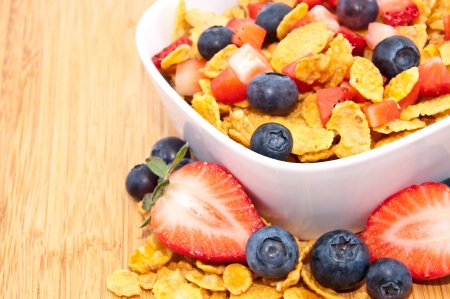 Heap of Cornflakes with fruits (Strawberries and Blueberries) in a bowl photo
