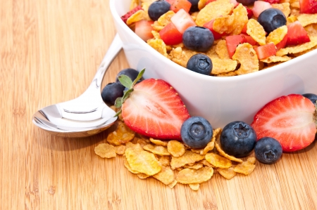 Heap of Cornflakes with fruits (Strawberries and Blueberries) and a spoon in a bowl Stock Photo - 13699420
