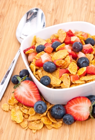 Heap of Cornflakes with fruits (Strawberries and Blueberries) and a spoon in a bowl photo