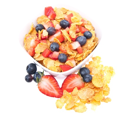 Cornflakes with fresh fruits in a bowl isolated on white background photo