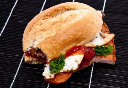 semmel: Roll with meat loaf, fried egg, parsley and ketchup on black tablecloth