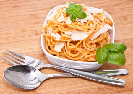 Fresh spaghetti with pesto rosso sauce on wooden background photo
