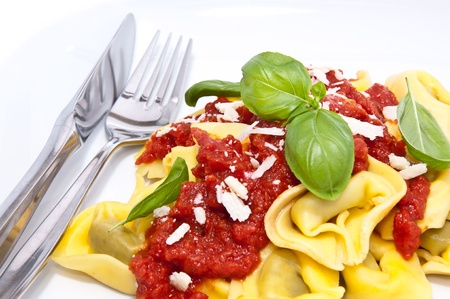 Tortellini with tomato sauce and Parmesan Cheese on a plate photo