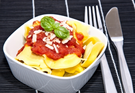 Tortellini with tomato sauce in a bowl on black background photo