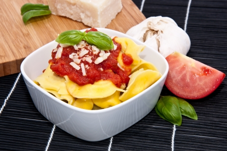 Tortellini in a bowl with ingredients on a black tablecloth photo