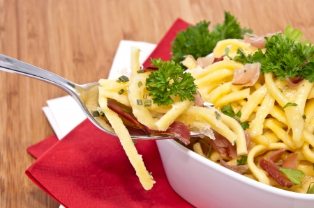 curren: Cheese Spaetzle in a bowl with portion on fork (on wooden background)