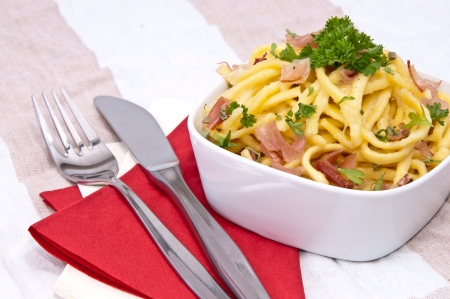 curren: Cheese Spaetzle with fresh herbs on red striped tablecloth Stock Photo