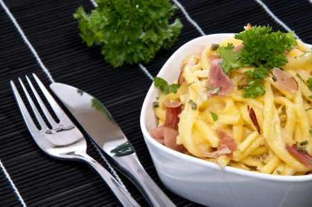 curren: Cheese Spaetzle in a Bowl decorated with Parsley and cutlery on a black tablecloth Stock Photo