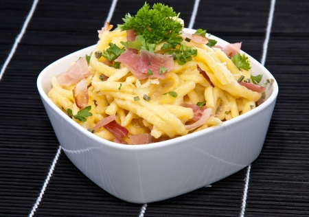 curren: Portion of Cheese Spaetzle on black background Stock Photo