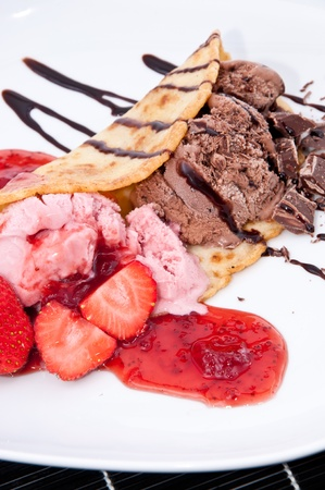 Homemade Strawberry and Chocolate Ice Cream on a plate against black background photo