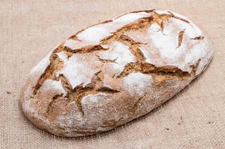 Loaf of bread on textile background photo