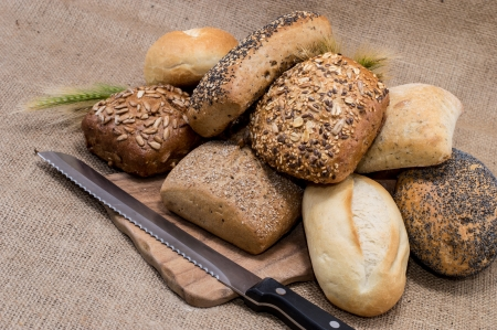 sustenance: Heap of rolls on cutting board with knife on a textile background Stock Photo