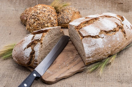 Halved loaf of bread on textile background photo