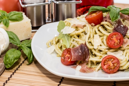 Spaghetti with Pesto Sauce and ingredients in the background photo