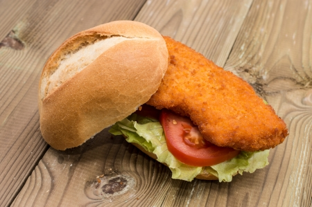 Sandwich with fried meat on wooden background photo