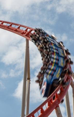 Rollercoaster in motion against blue sky photo