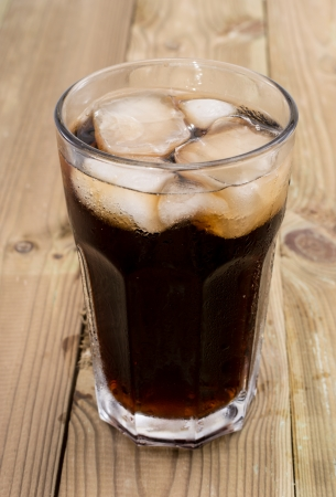 soft drinks: Cold Beverage with ice on wooden background