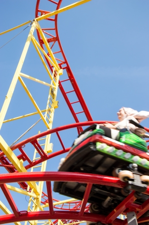 Peoples riding on a rollercoaster with blue sky in the background