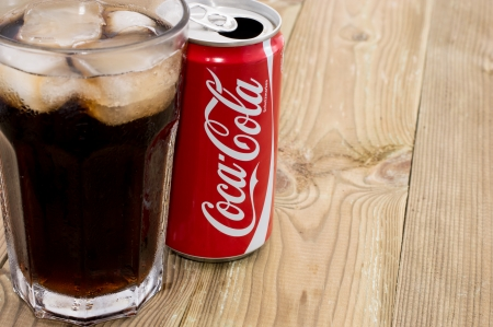 Coca Cola can with Cola in a glass in wooden background