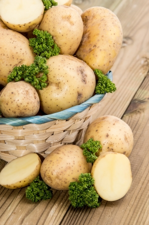 unpeeled: Fresh Potatoes and Parsley in a basket on wooden background Stock Photo