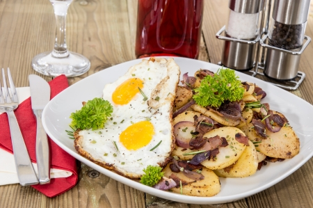 Plate with fried Potatoes and Eggs on wooden background photo