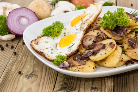 chippy: Plate with fried Potatoes and Eggs on wooden background