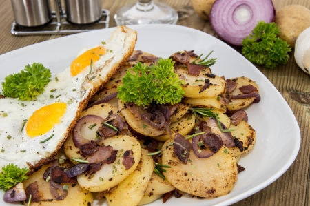 Fried Egg on a heap of roasted Potatoes on wooden background photo
