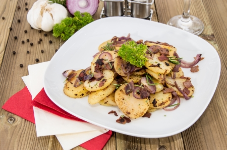 Fried Potatoes with blurred ingredients in the background photo
