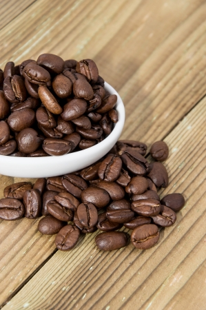 Small bowl with Coffee Beans on wooden background photo