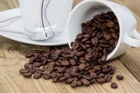 Cup filled with Coffee Beans on wooden background photo