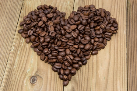 Heart formed out of Coffee Beans on wooden background photo