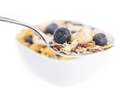 Muesli with Blueberries on a spoon and blurred bowl in the background isolated on white photo