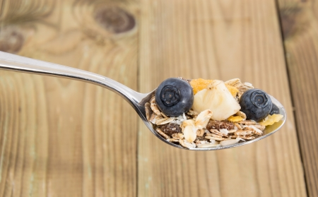 Mixed Muesli on a spoon on wooden background photo