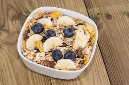 Breakfast consisting of Muesli and Fruits on wooden background photo