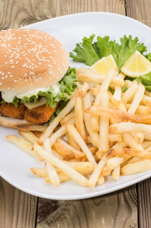Fish Burger with Chips on a plate on wooden background photo